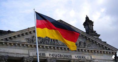 Powiewająca flaga niemiec na tle budynku rządowego.